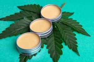 cannabis salve with hemp and cbd oil on green background